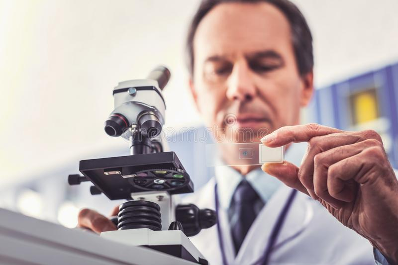 Химик тщательно изучая генетический код стоковые фото