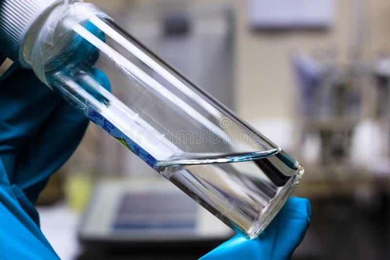 Химическая прозрачная жидкость в ясной бутылке держа химией стоковая фотография rf