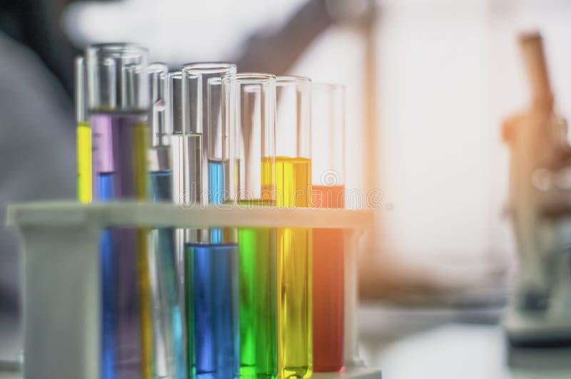 Химическая трубка, положила дальше таблицу, с красочными жидкостями, в стеклянные лампы для косметик от тетрадей, в лаборатории,  стоковое фото rf