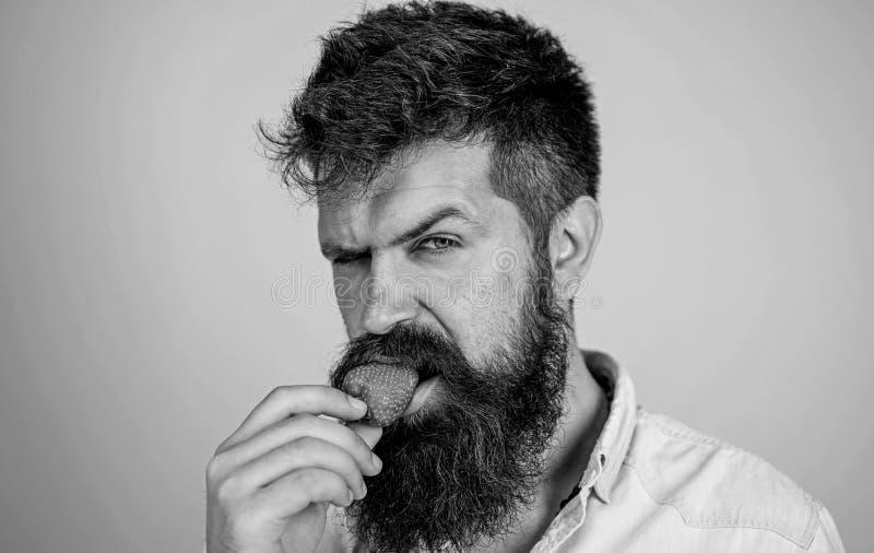 Хипстер красивой строгой стороны человека сексуальный с длинной клубникой попытки бороды Гастрономическое удовольствие Концепция  стоковое фото rf