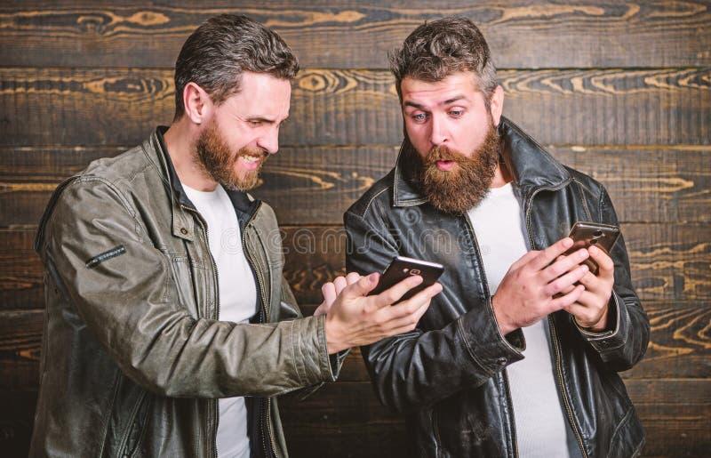 Хипстер людей зверский бородатый в модных кожаных куртках использует мобильный интернет E : o стоковая фотография