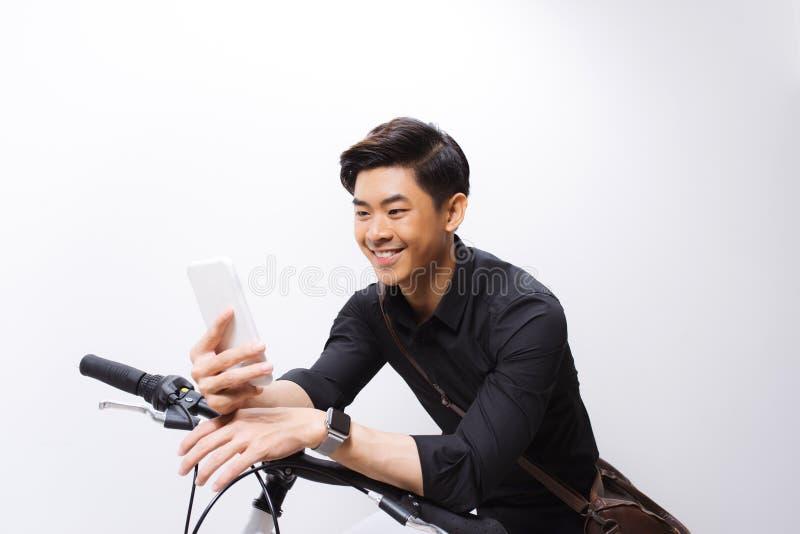 Хипстер отправляя SMS кто-то на его велосипеде стоковая фотография