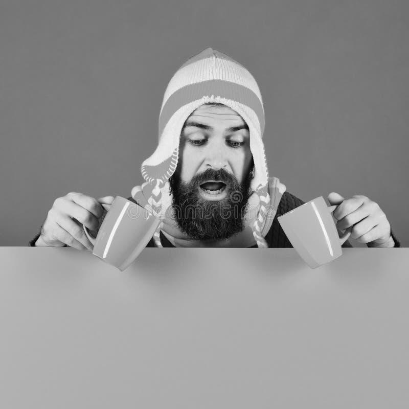Хипстер с бородой и любопытным лицом, пьющий кофе стоковое фото