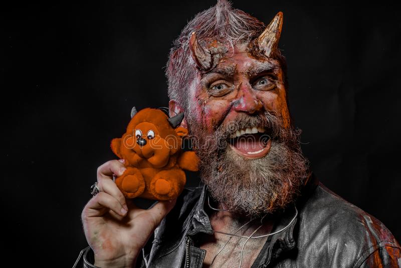 Хипстер хеллоуина с satan рожками, кровопролитные раны держит мягкое чудовище стоковое фото rf