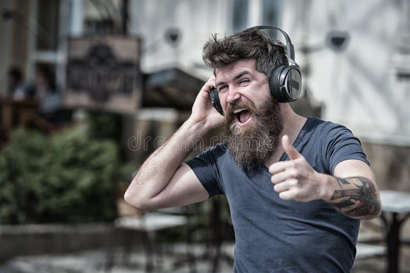 Хипстер человека бородатый с музыкой наушников слушая Хипстер наслаждается высококачественным звуком песни в наушниках Получите м стоковое фото