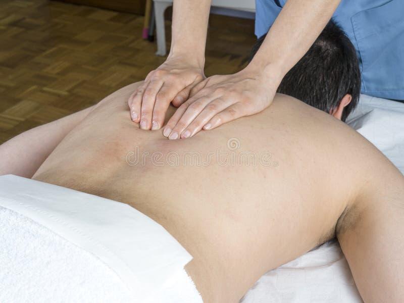 Хиропрактор, физиотерапевт дает задний массаж стоковая фотография
