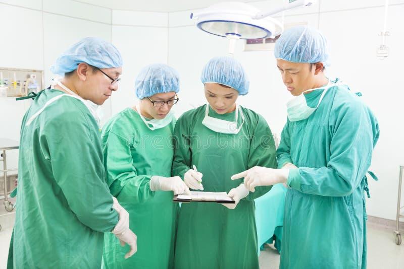 Хирурги обсуждая показатели пациента в комнате деятельности стоковые фотографии rf