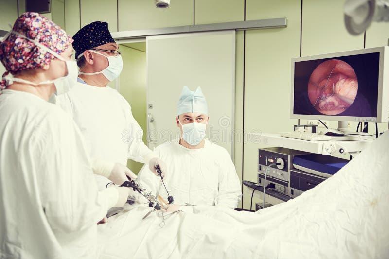 Хирурги объединяются в команду руки во время laparoscopic подбрюшной деятельности в хирургии ребенка стоковые фотографии rf