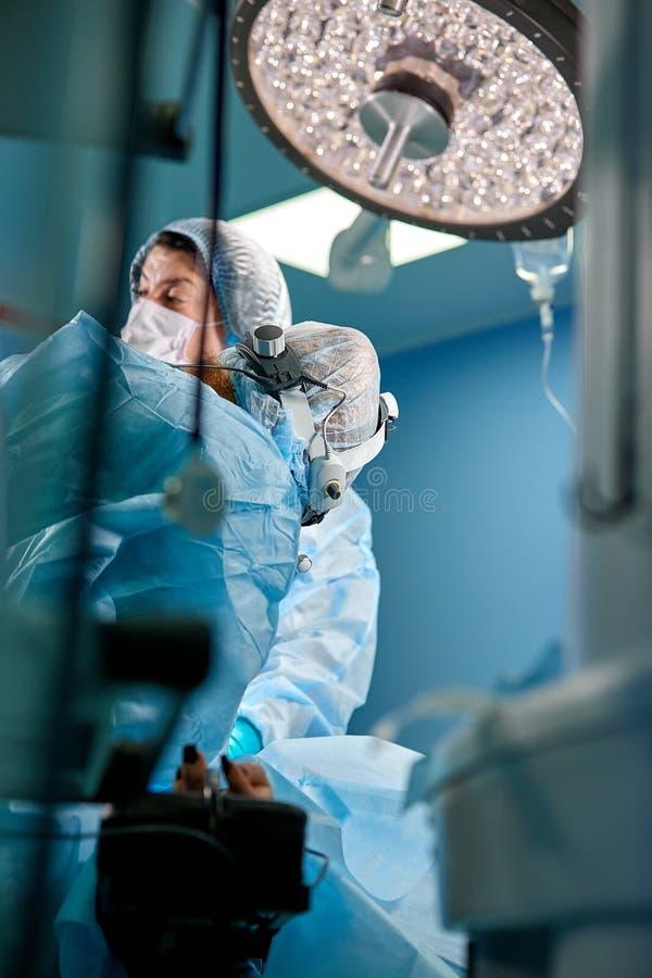 Хирург выполняя пластическую хирургию в операционной больницы Хирург в loupes маски нося во время медицинского procadure стоковое фото