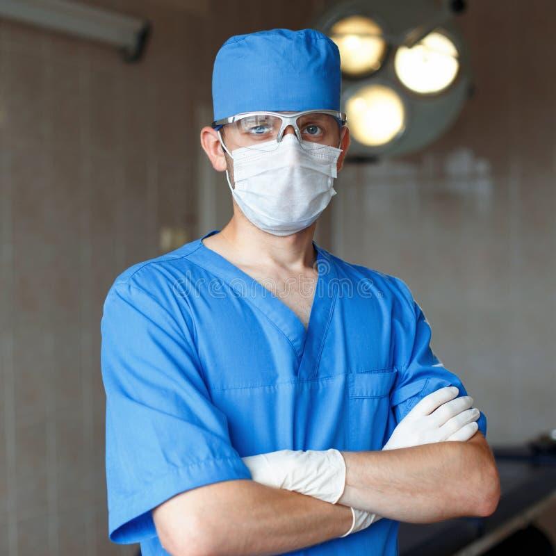 Хирург в голубых форме, стеклах и шляпе стоит стоковое изображение rf
