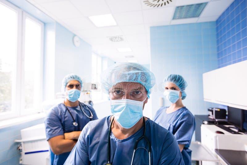 Хирург и медсестры стоя в больнице стоковое фото