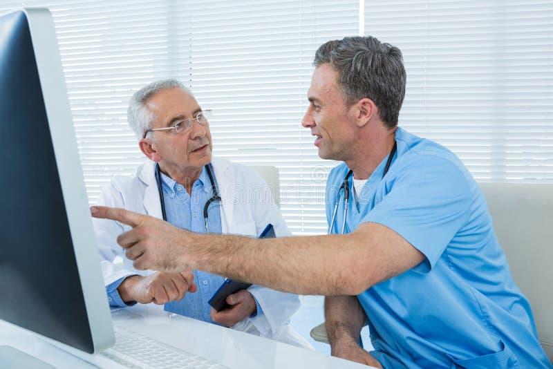 Хирург и доктор обсуждая над персональным компьютером стоковые фото