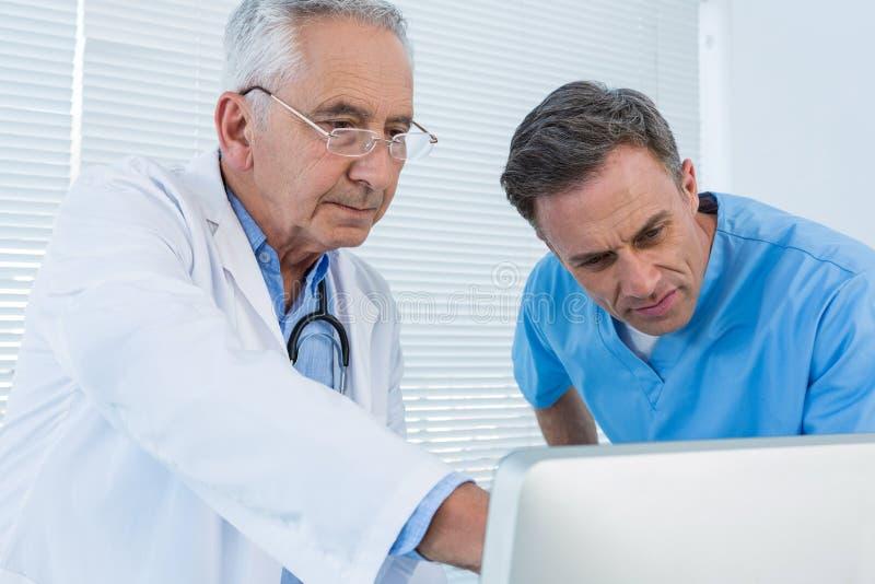 Хирург и доктор обсуждая над персональным компьютером стоковое изображение rf