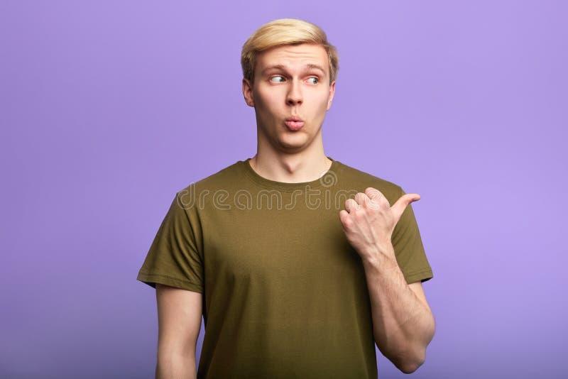 Хитрый красивый свистеть человека, указывая на сторону с большим пальцем руки вверх стоковое фото rf