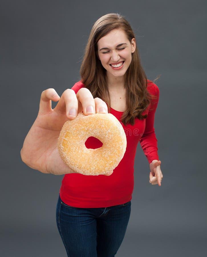 Хихикая молодая женщина хватая донут как заманчивость высококалорийной вредной пищи стоковые фото