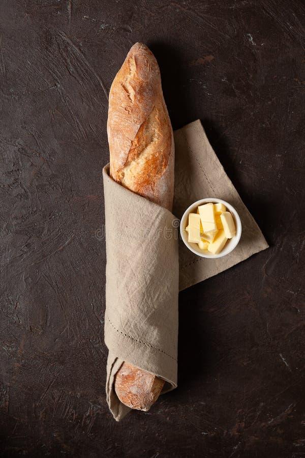 Хлебец домодельного хлеба или багета С маслом На темной текстурированной или коричневой предпосылке стоковые изображения