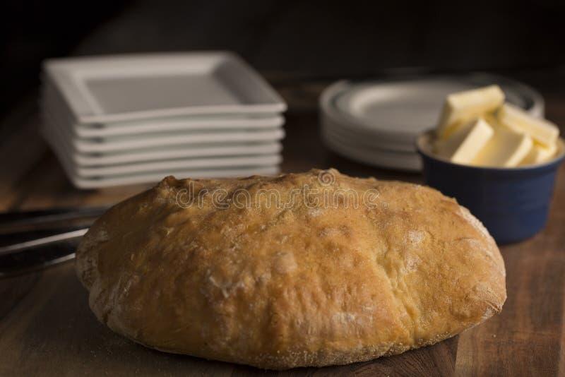 Хлебец итальянского хлеба Pugliese деревенский полный с маслом на деревянной разделочной доске стоковая фотография rf