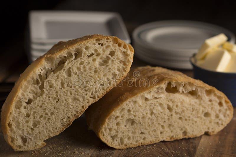 Хлебец итальянского хлеба Pugliese деревенский половинный на деревянной разделочной доске стоковое фото