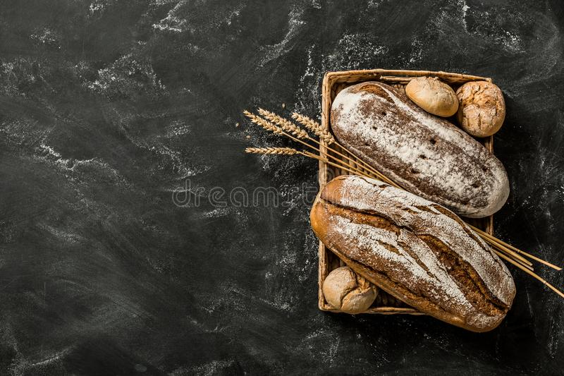 Хлебопекарня - деревенские покрытые коркой ломти хлеба и плюшки на черноте стоковое фото rf