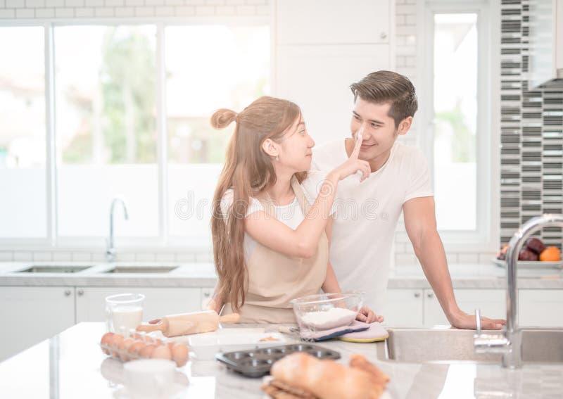 Хлебопеки пар молодых азиатских пар счастливые любящие помогая сделать обедающий стоковые изображения