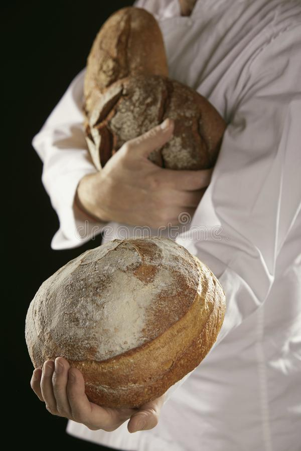 Хлебопек в белом свежем хлебе нося стоковые изображения rf
