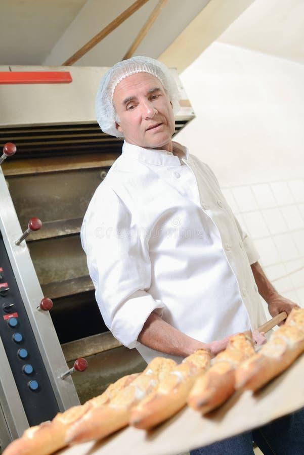 Хлебопек извлекая хлеб от печи стоковая фотография