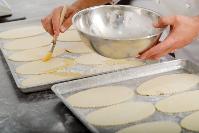 Хлебопек прикладывая желток с щеткой стоковая фотография