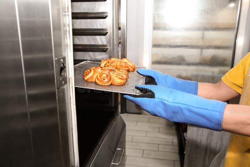 Хлебопек принимая вне поднос с печеньем от печи в мастерской стоковые фото