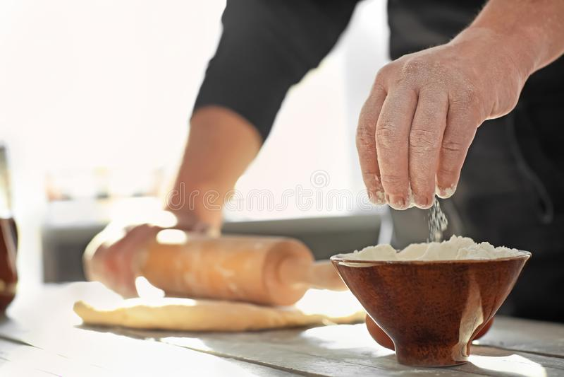 Хлебопек принимая муку от шара пока свертывающ тесто на кухонном столе стоковые фотографии rf