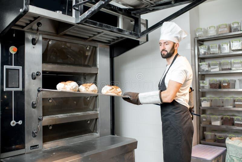Хлебопек принимая хлебы от печи стоковое фото