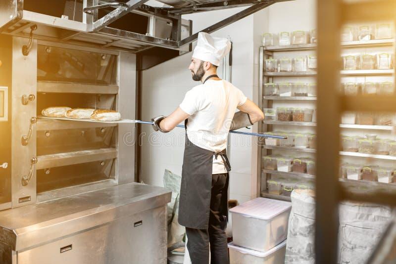 Хлебопек принимая хлебы от печи стоковая фотография