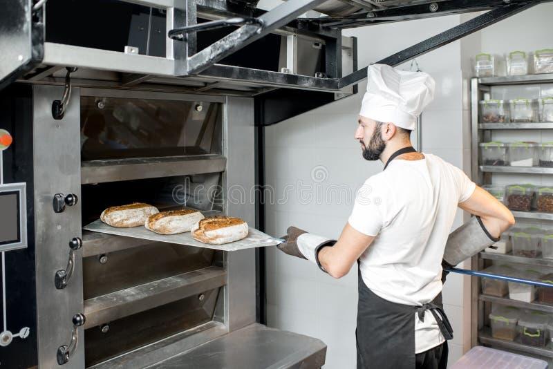 Хлебопек принимая хлебы от печи стоковые изображения