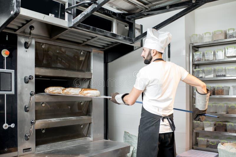 Хлебопек принимая хлебы от печи стоковые фотографии rf