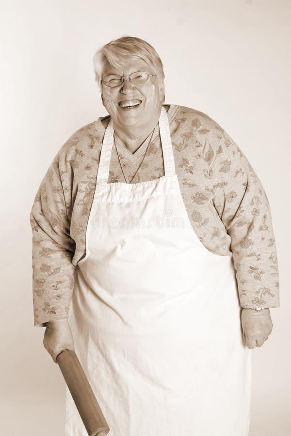 хлебопек смеясь над старшей женщиной стоковые изображения