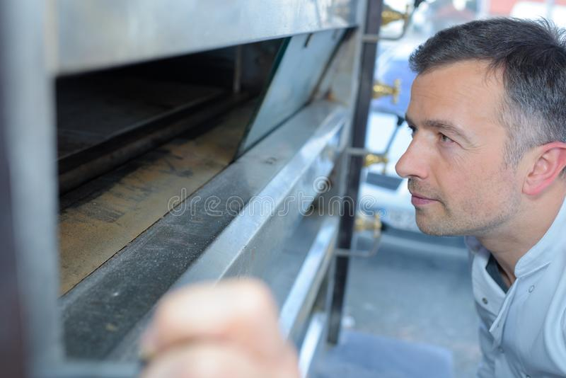 Хлебопек смотря в хлебной печи стоковое фото rf