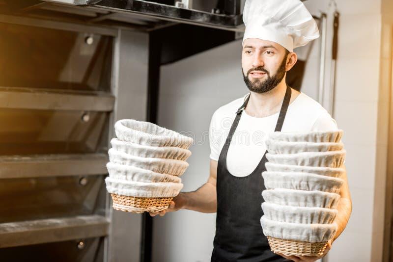 Хлебопек с формами выпечки на хлебопекарне стоковое изображение rf
