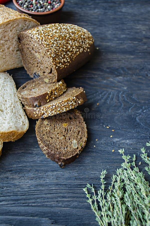 Хлебцы черно-белого хлеба на черной предпосылке доски Натюрморт, захваченный сверху стоковая фотография