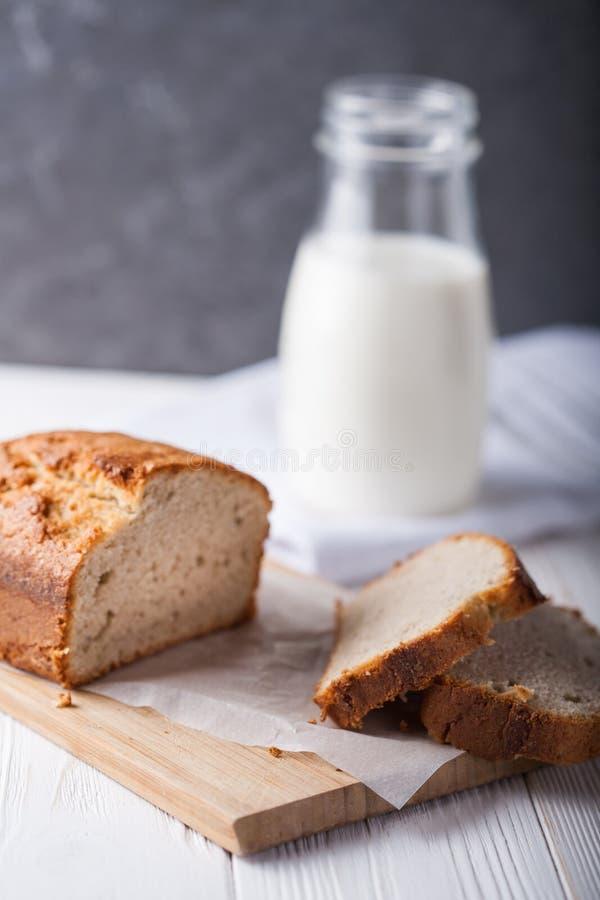 Хлеб банана в лотке с белой пергаментной бумагой на белом деревянном столе с бутылкой молока на заднем плане конец вверх стоковое фото rf