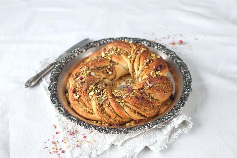 Хлеб венка на винтажном подносе с завалкой фисташки стоковая фотография
