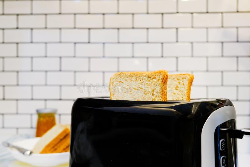 Хлеб всей пшеницы на тостере с бутылкой оранжевого варенья для здоровой предпосылки кирпичной стены завтрака дома белой стоковые изображения rf
