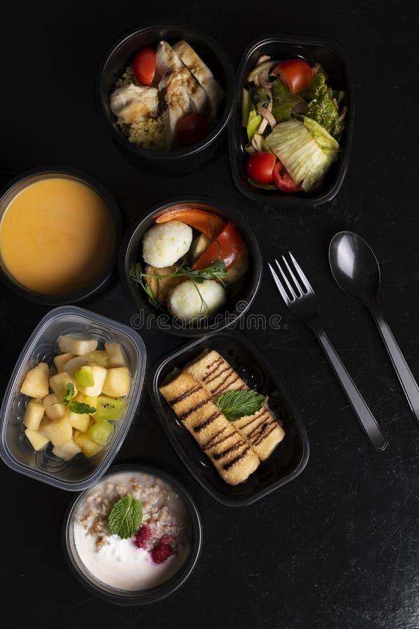 хлеб зерна, oatmeals, суп тыквы с испаренными овощами, салат и экзотический фруктовый салат на черной таблице стоковые фотографии rf