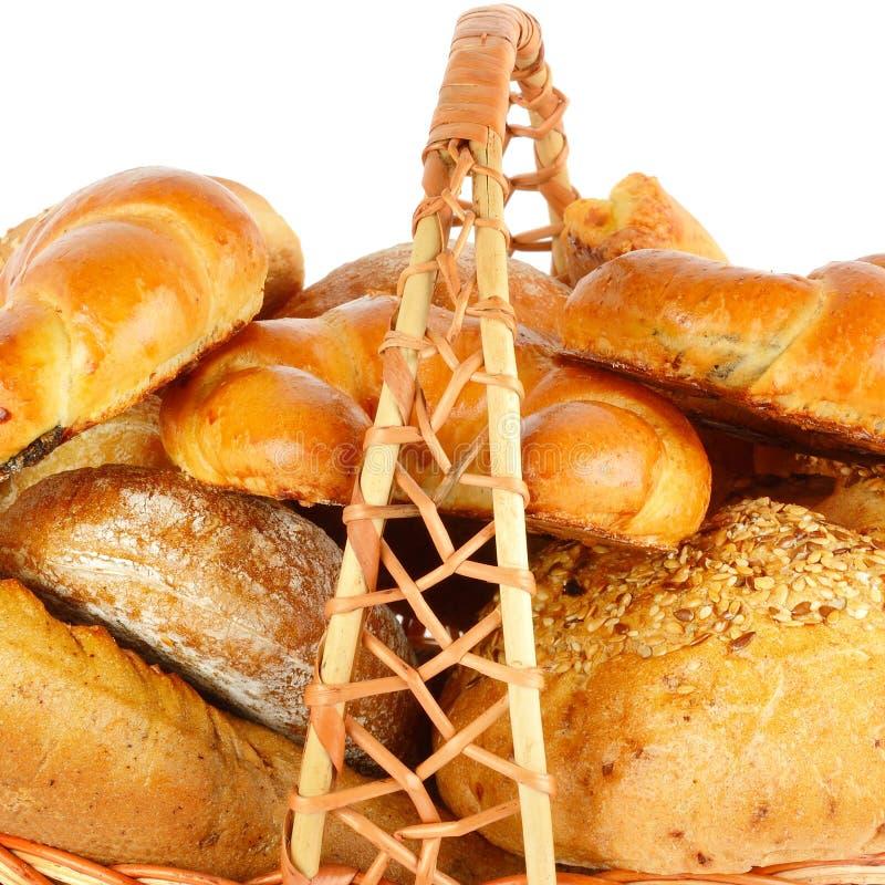Хлеб и хлебобулочные изделия в плетеной корзине изолированной на белом bac стоковая фотография