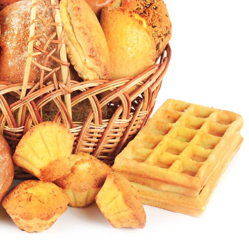 Хлеб и хлебобулочные изделия в плетеной корзине изолированной на белом bac стоковые изображения rf