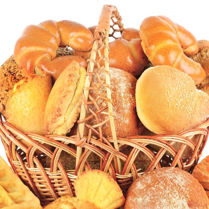 Хлеб и хлебобулочные изделия в плетеной корзине изолированной на белом bac стоковое изображение rf
