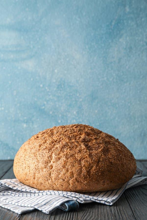 Хлеб на полотенце кухни на деревянном столе против светлой предпосылки стоковые изображения rf
