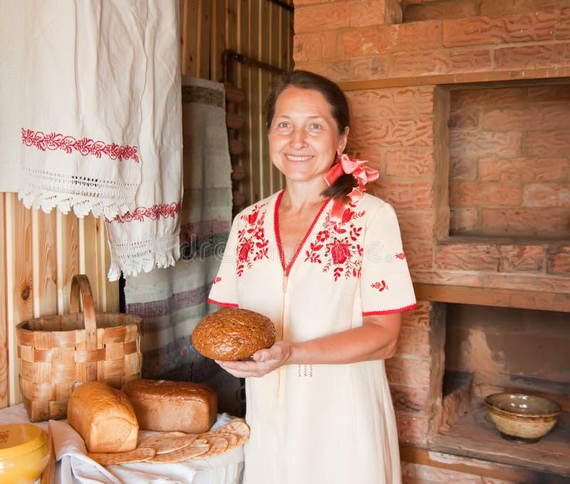 хлеб около женщины печки традиционной стоковое изображение