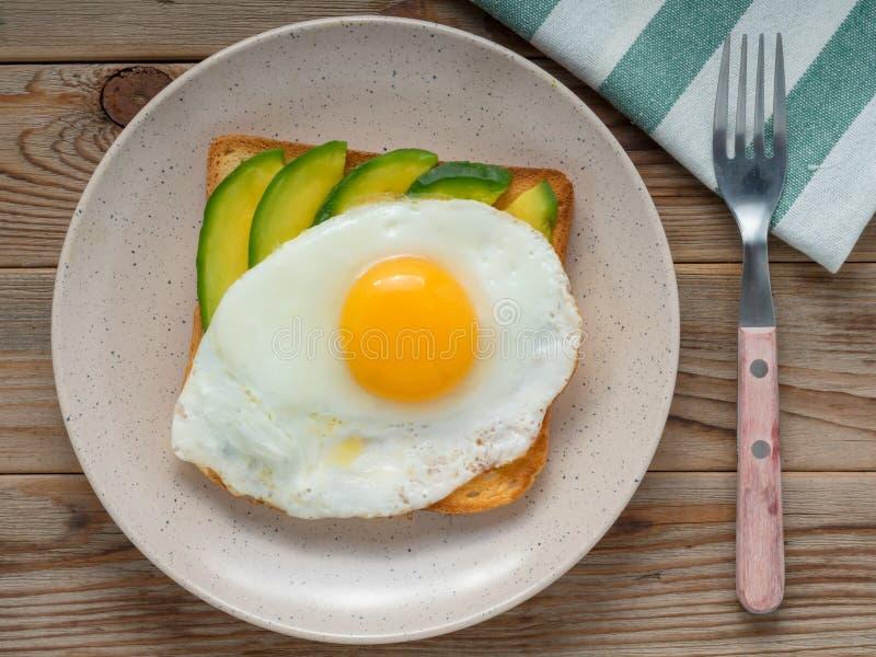 Хлеб с яичницами, авокадо здравицы И куски огурца на деревянном столе Взгляд сверху стоковые фотографии rf