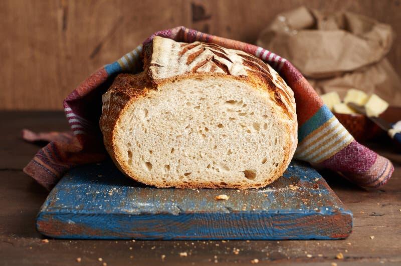 Хлеб тоста sourdough ремесленника на голубой деревянной разделочной доске с маслом и розовым гималайским солью стоковое фото