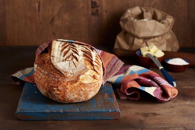 Хлеб тоста sourdough ремесленника на голубой деревянной разделочной доске с маслом и розовым гималайским солью стоковые изображения rf