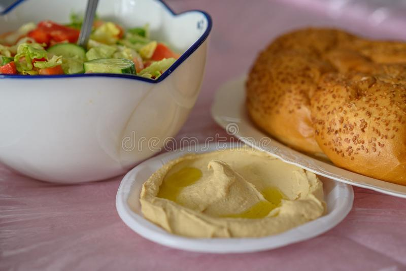 Хлеб Challah на таблице для еды Shabbat и традиционное домодельное hummus, салат на розовой таблице Еврейская кухня стоковое фото